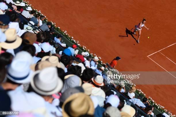 TOPSHOT The crowd watches Romania's Simona Halep return the ball to Latvia's Jelena Ostapenko during their final tennis match at the Roland Garros...