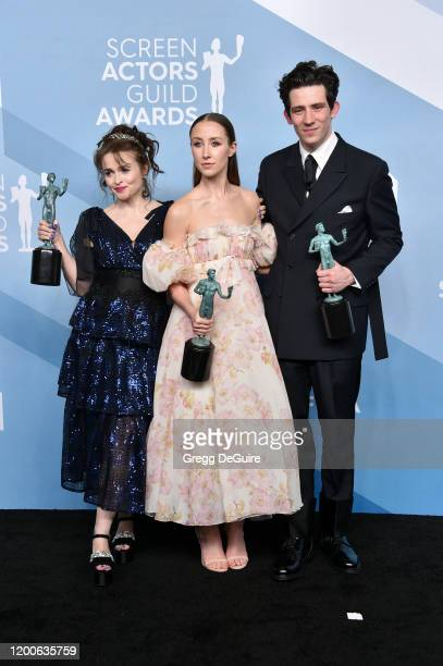 The Crown cast Helena Bonham Carter Josh O'Connor and Erin Doherty pose in the press room with the trophy for Outstanding Performance by an Ensemble...