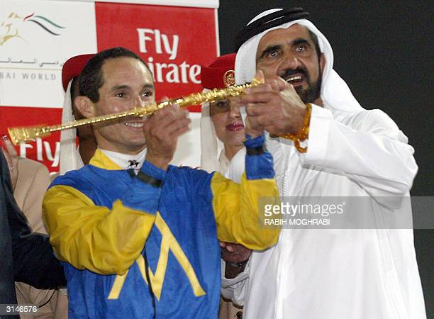The Crown Prince of Dubai and UAE Defense Minister Sheikh Mohammed bin Rashed alMaktoum raises the trophy with US jockey Alex Solis after he won the...
