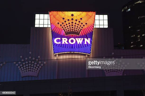 The Crown Resorts Ltd logo is displayed at the Crown Melbourne casino and entertainment complex at night in Melbourne Australia on Friday Aug 7 2015...