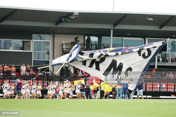 The Crows banner splits aprt in the strong wind as Crows players enter the field during the round two AFLW match between the Melbourne Demons and the...