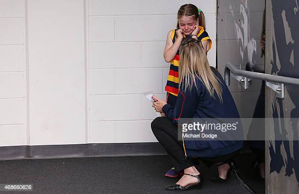 The Crows mascot cries before walking out with Taylor Walker of the Crows during the round one AFL match between the Adelaide Crows and the North...