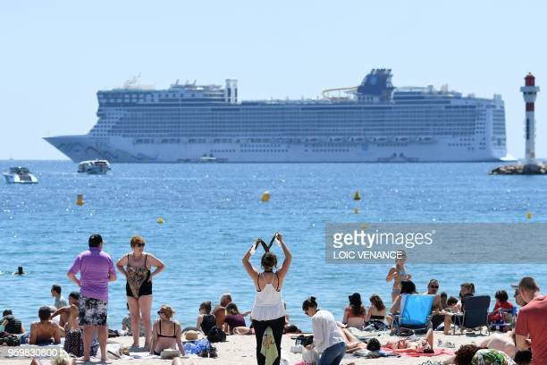 The cruise liner Norwegian Epic is anchored off shore as people enjoy the beach on May 18 2018 during the 71st edition of the Cannes Film Festival in...