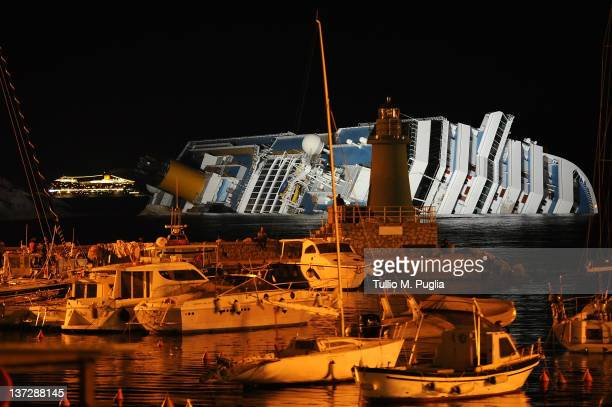 The cruise ship Costa Serena navigates off the shore of the island of Giglio as her sister ship Costa Concordia lies stricken on January 18 2012 in...