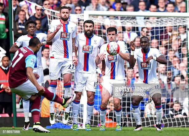 The Crystal Palace wall prepares to jump to block West Ham United's French midfielder Dimitri Payet's freekick but cannot prevent him scoring their...