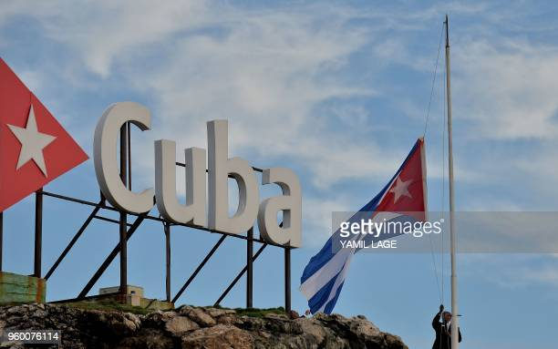 The Cuban national flag is raised at halfmast in tribute to the victims of a plane that crashed shortly after taking off from Jose Marti airport and...