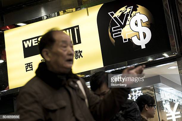 The currency symbols for the Chinese yuan and Hong Kong Dollar sit on a sign outside a currency exchange store in Hong Kong China on Tuesday Jan 12...