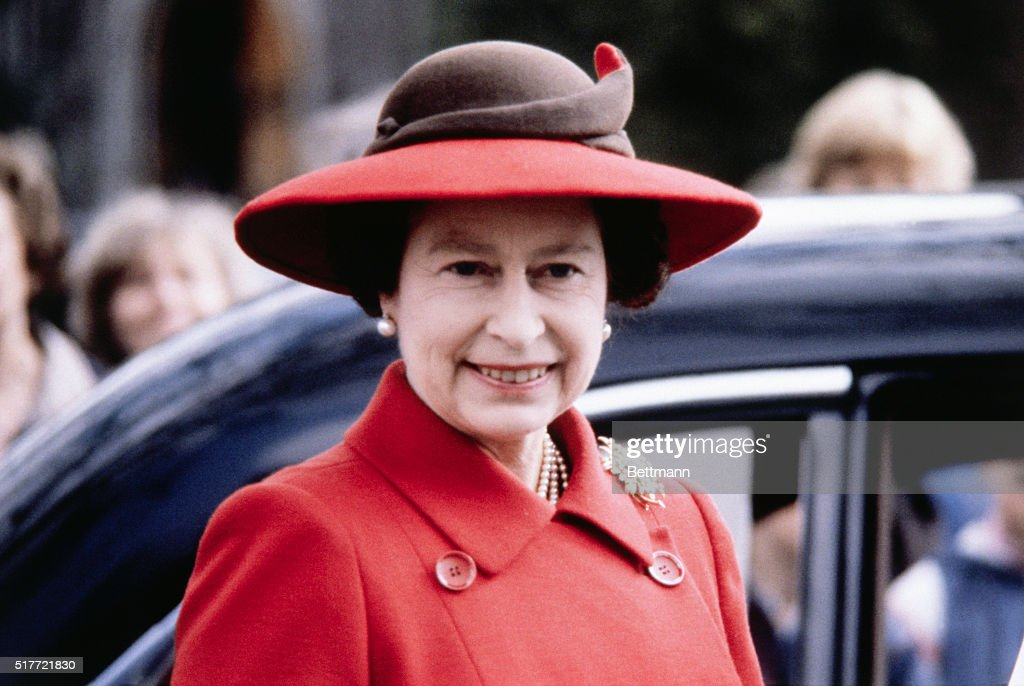 The current monarch of England, Queen Elizabeth II, in red coat and matching broad-brimmed hat, in London in 1981.