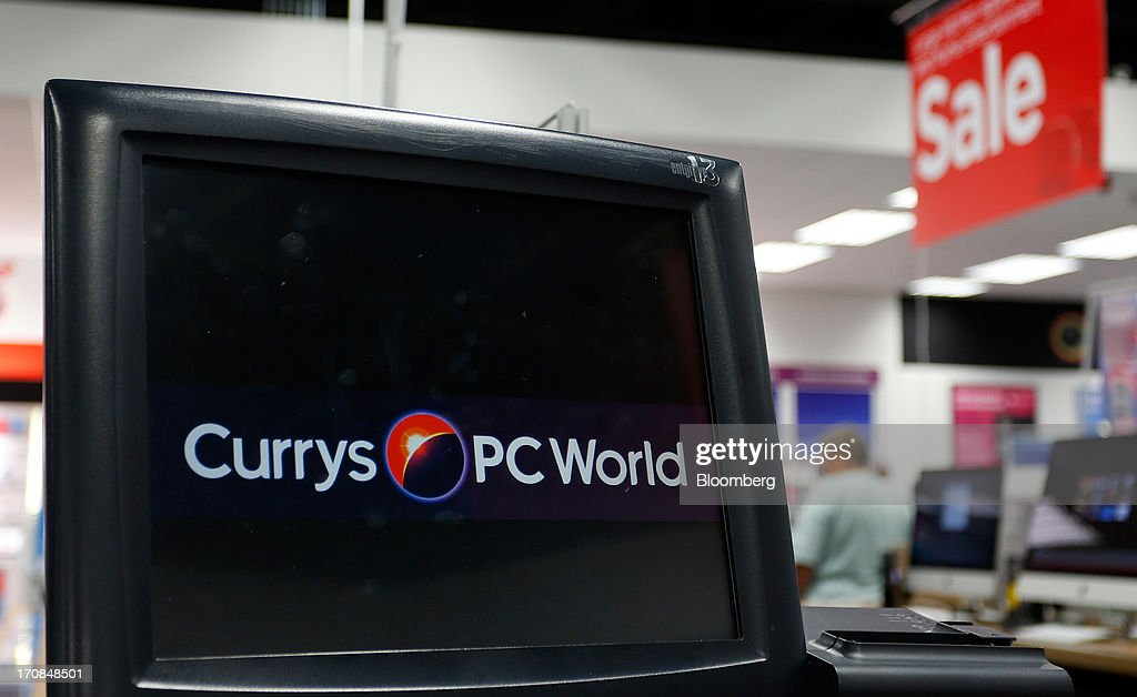 The Currys and PC World logos are displayed on the screen of a cash register inside a Currys and PC World 2 in 1 store, operated by Dixons Retail Plc, in Manchester, U.K., on Tuesday, June 18, 2013. Dixons Retail Plc, the U.K.'s largest consumer-electronics retailer, said last month it will report annual pretax profit at the 'top end' of analysts' predictions after fourth-quarter revenue beat estimates on increased sales of tablets and services such as software tutorials. Photographer: Paul Thomas/Bloomberg via Getty Images