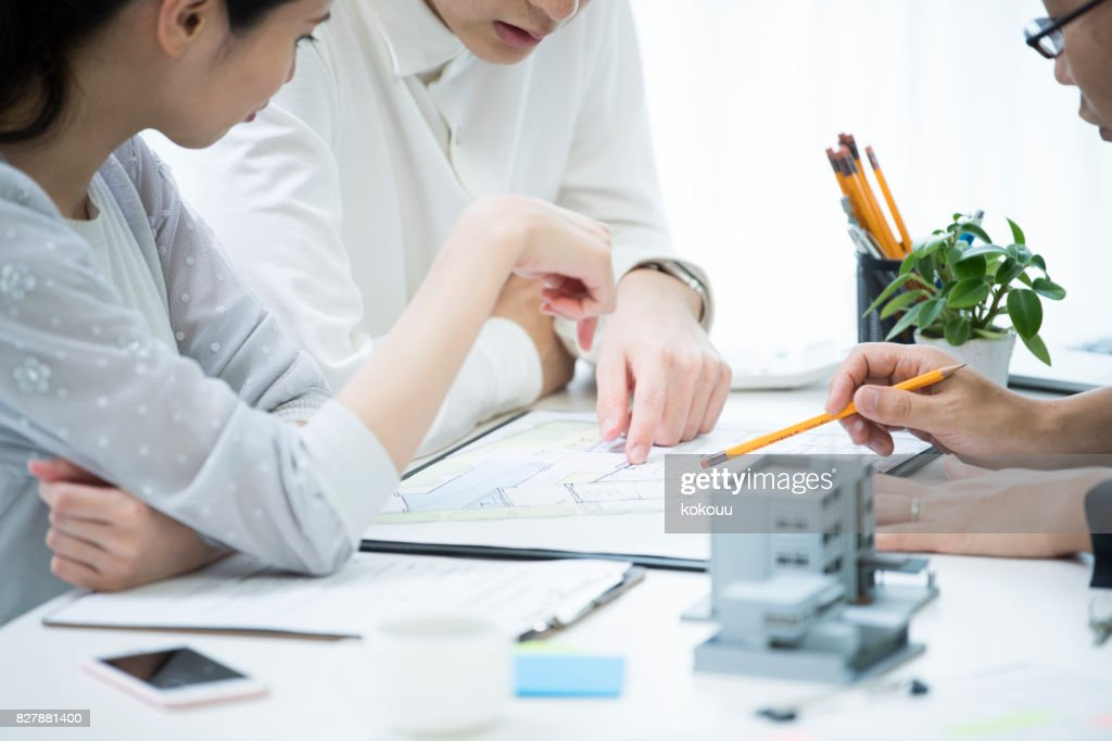 The customer and the employee are discussing the materials by looking at the materials. : Stock Photo