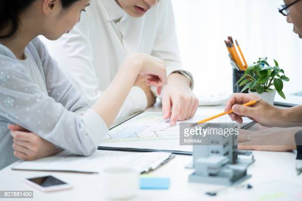 the customer and the employee are discussing the materials by looking at the materials. - real estate stock pictures, royalty-free photos & images