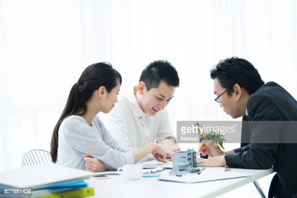 the customer and the employee are discussing the materials by looking at the materials. - real estate office stock photos and pictures
