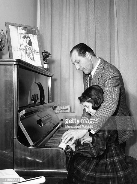 The cyclist Gino Bartali playing the piano with his daughter Bianca Maria. Florence, March 1963