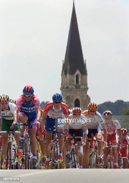 The cyclists of the 86th Tour de France pass nearby a church during the third stage of the 'Grande Boucle' between Nantes and Laval western France 06...