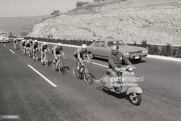The cyclists of the Italian team are training in groups on the Mexican roads prior to the Olympic competitions by following a Vespa driven by the...