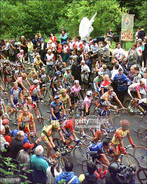 the cyclists of the Tour de France stop near the monument built in memory of Italian cyclist Fabio Casartelli in the Portet d'Aspet pass near Luchon...
