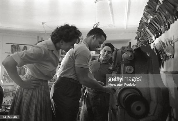 The Czechoslovakian discus thrower Olga Fikotova looking at her husband the American hammer thrower Harold Connolly trying a machinery in a shoe shop...