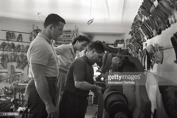 The Czechoslovakian discus thrower Olga Fikotova together with her husband the American hammer thrower Harold Connolly looking at a shoemaker working...