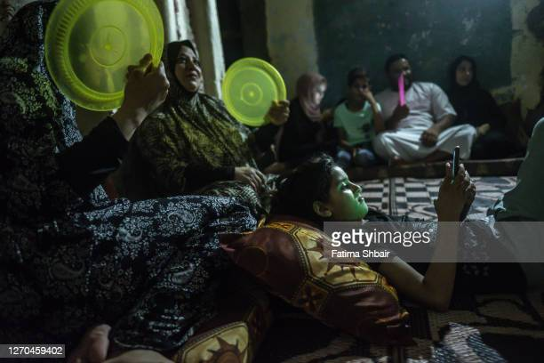 The Dahlan family uses plastic trays to fan themselves under LED light due to overheating and power cuts in Jabalia Refugee Camp on on August 28,...