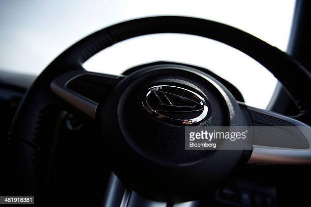 The Daihatsu Motor Co logo sits on the steering wheel of a prototype of the company's Copen convertible sports minicar during a media preview in...