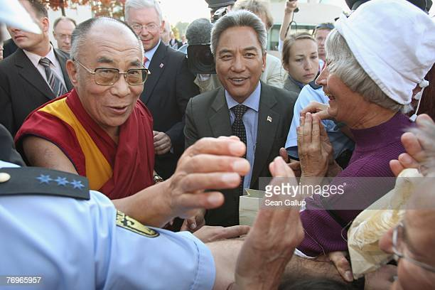 The Dalai Lama greets wellwishers outside the Chancellery after a private meeting with German Chancellor Angela Merkel September 23 2007 in Berlin...