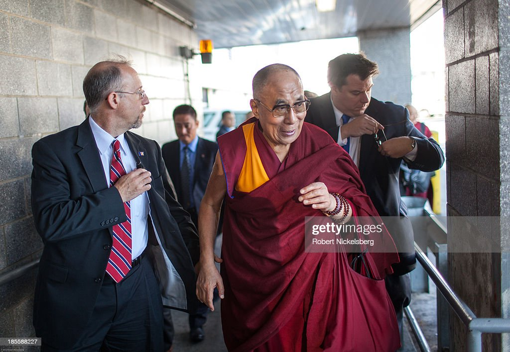 The Dalai Lama (C) is escorted to his plane by U.S. Department of State diplomatic security before leaving for Germany October 21, 2013 at JFK Airport in New York City. The Dalai Lama was in New York City for three days of his Buddhist teachings that ran October 18-20.