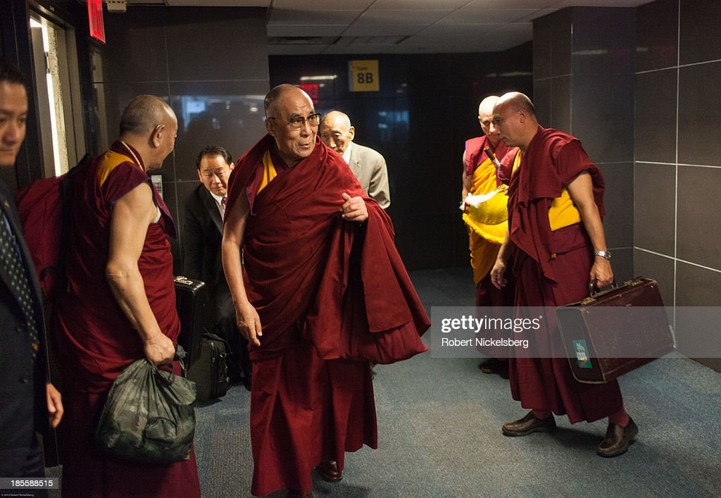 The Dalai Lama is escorted to his plane to Germany by Tibetan monks October 21, 2013 at JFK Airport in New York City. The Dalai Lama was in New York City for three days of his Buddhist teachings that ran October 18-20.