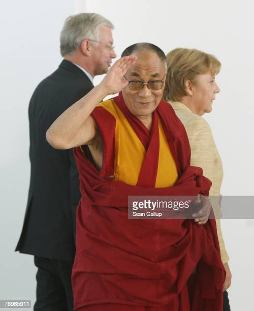 The Dalai Lama looks back while walking with German Chancellor Angela Merkel and Hessen Governor Roland Koch after private talks at the Chancellery...