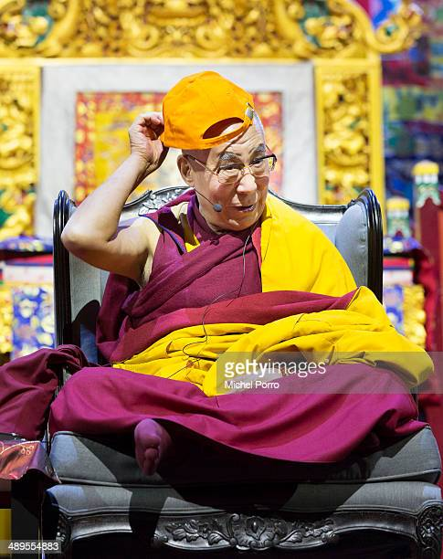 The Dalai Lama puts on a cap with the Dutch national color orange on the second day of his threeday visit on May 11 2014 in Rotterdam Netherlands
