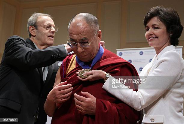 The Dalai Lama recieves the the Democracy Service Medal from National Endowment for Democracy President Carl Gershman and Judy Shelton Vice President...