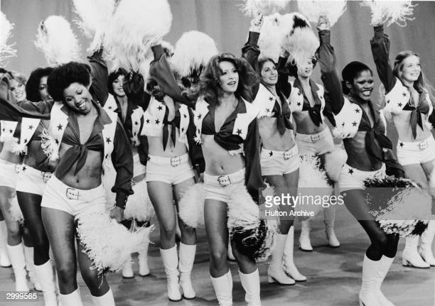 The Dallas Cowboy Cheerleaders perform on stage in matching costumes cheering and shaking pompoms 1970s