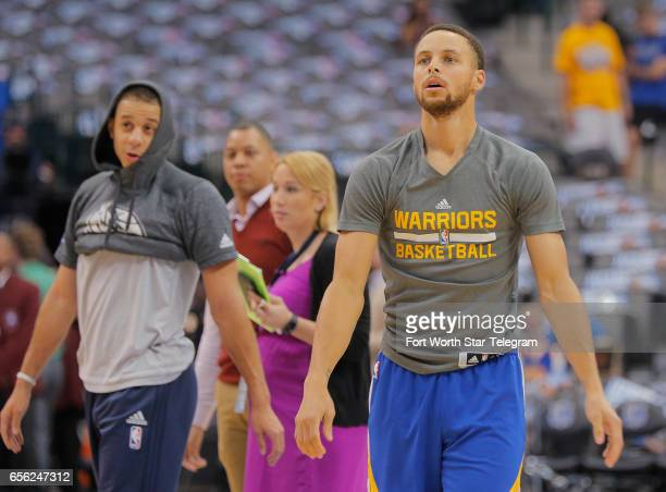 The Dallas Mavericks' Seth Curry left walks by as his brother Golden State Warriors guard Stephen Curry right shoots warmup shots as the Mavericks...