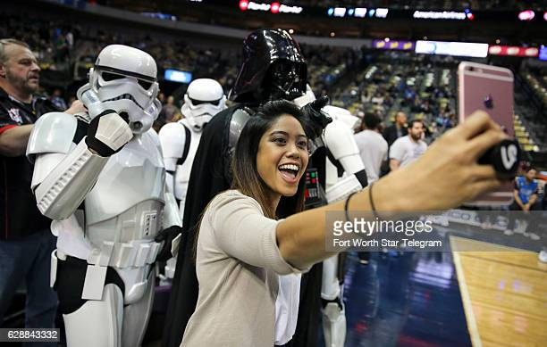 The Dallas Mavericks' social media coordinator Lizelle Lauron takes a selfie with members of the 501st Legion dressed as Darth Vader and various...
