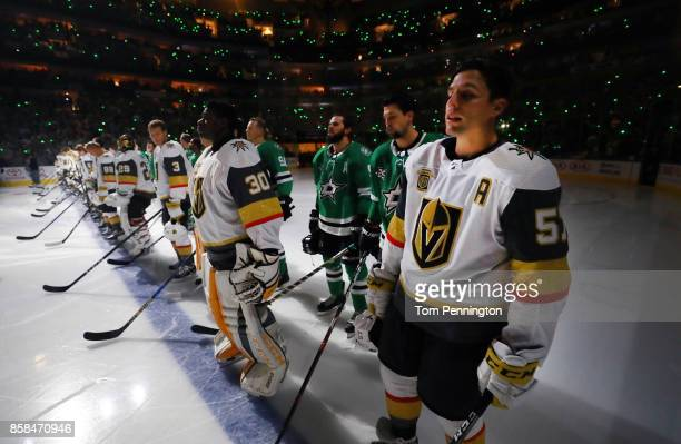The Dallas Stars stand behind the Vegas Golden Knights on the ice during the National Anthem at American Airlines Center on October 6 2017 in Dallas...
