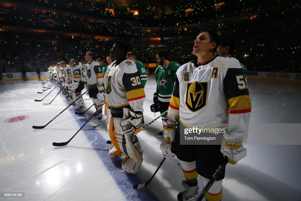 The Dallas Stars stand behind the Vegas Golden Knights on the ice during the National Anthem at American Airlines Center on October 6, 2017 in Dallas, Texas.