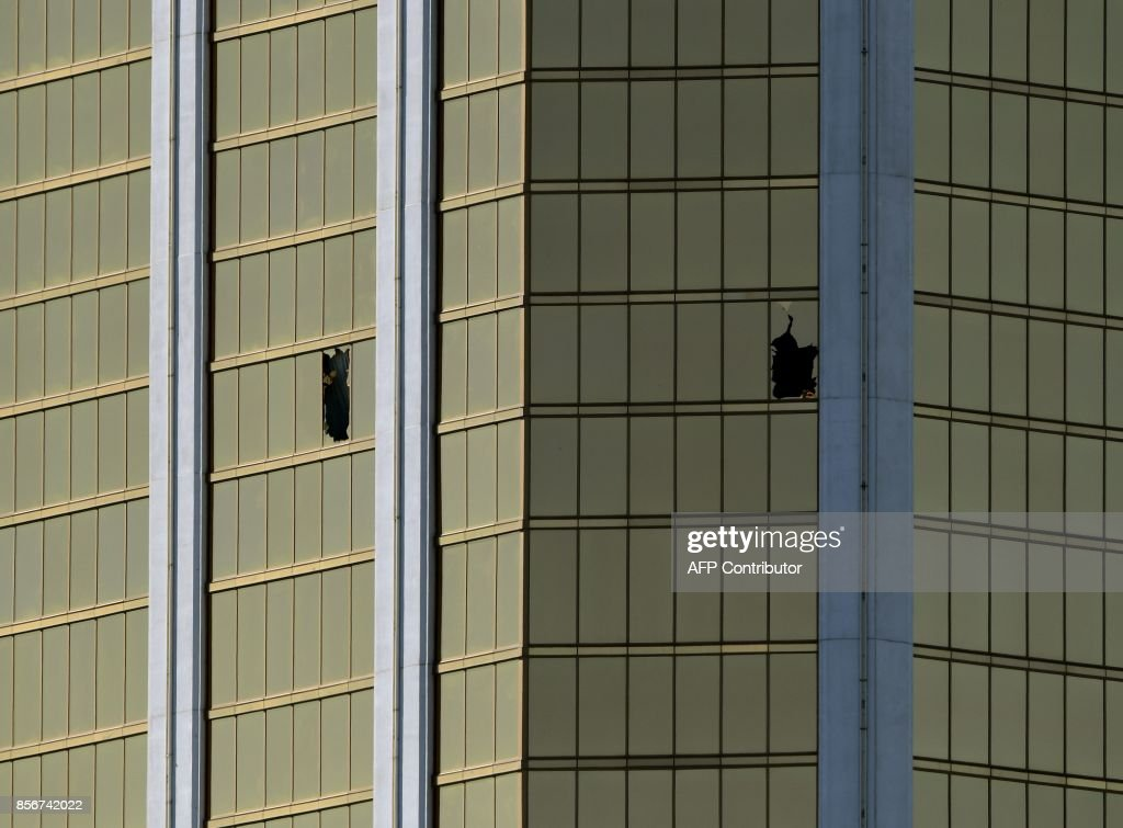 The damaged windows on the 32nd floor room that was used by the shooter in the Mandalay Hotel after a gunman killed at least 58 people and wounded more than 500 others when he opened fire on a country music concert in Las Vegas, Nevada on October 2, 2017. Police said the gunman, a 64-year-old local resident named as Stephen Paddock, had been killed after a SWAT team responded to reports of multiple gunfire from the 32nd floor of the Mandalay Bay, a hotel-casino next to the concert venue. / AFP PHOTO / Mark RALSTON