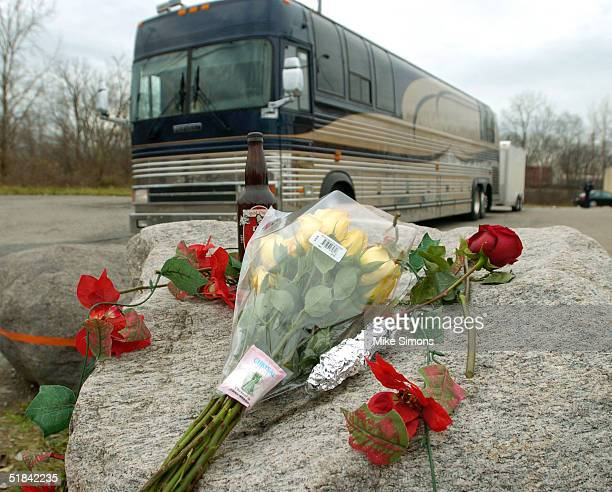 The Damageplan tour bus drives past a makeshift memorial outside of the Alrosa Villa nightclub the day after a gunman fired on the band Damageplan,...