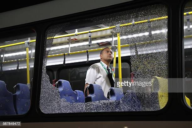 TOPSHOT The damages to the windows of an Olympic journalists bus hit while driving on the transolympica highway are inspected by an official in Rio...