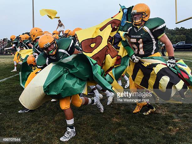 The Damascus Swarming' Hornets break through the banner as they are introduced before the season opener between Damascus and Quince Orchard High...