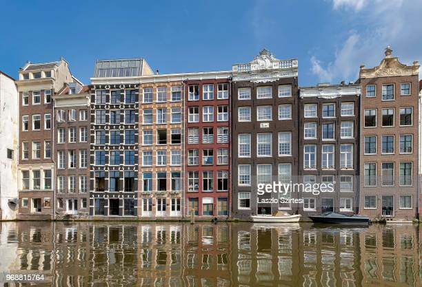 The Damrak Canal's houses are seen from a boat on May 30 2018 in Amsterdam Netherlands This group of canal houses is one of the bestknown buildings...