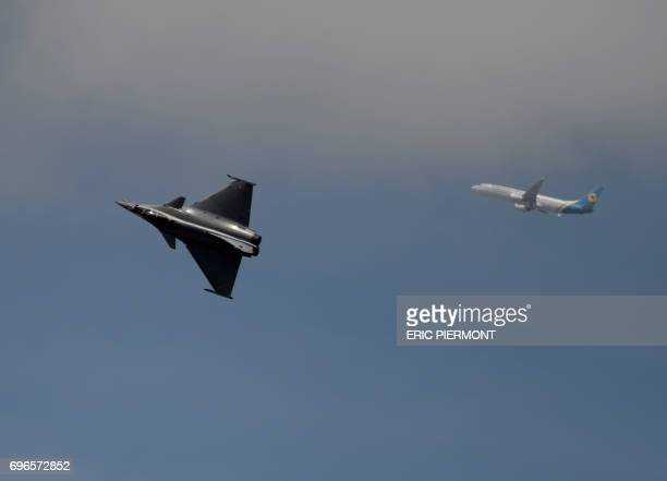 The Dassault Aviation Rafale jet fighter performs as a jetliner crosses the sky during a demonstration in Le Bourget on June 16 2017 prior to the...