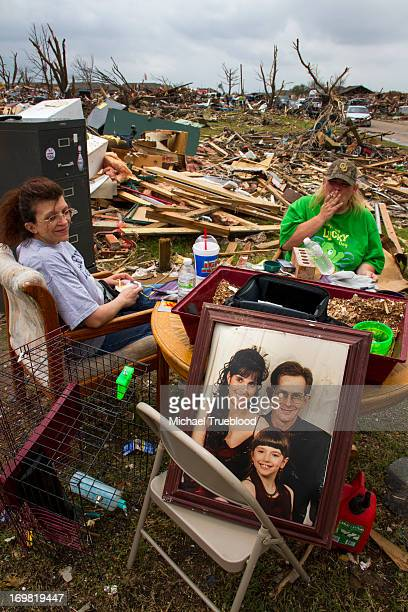 CONTENT] The daughter and daughterinlaw of James Moynihan sit before what is left of his house He survived the tornado by taking refuge in the...
