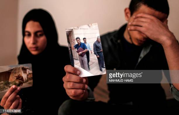 TOPSHOT The daughter and son of Zaki Mubarak hold his picture during an interview in their family home in Deir alBalah in central Gaza strip on April...