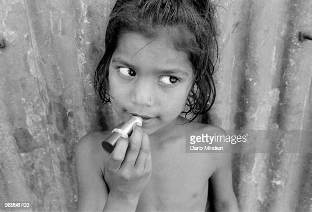 The daughter of a sexworker applying lipstick in Sonagachi district in Kolkata India 1996 Sonagachi translated as Golden Tree is the largest redlight...