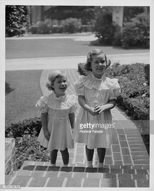 The daughter of actor Errol Flynn Arnella Roma and Deirdre wearing matching dress on the front steps of a house circa 1955