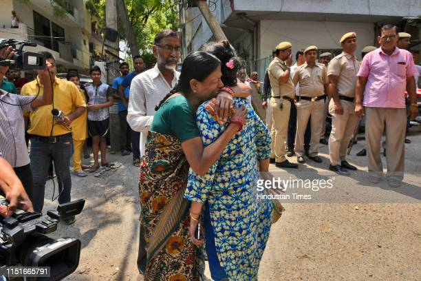 The daughter of an elderly couple who were found murdered along with their domestic help at their house, is comforted by a relative, at Vasant...