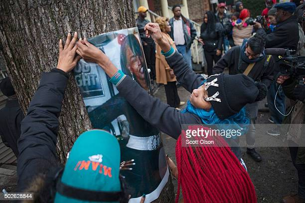 The daughters of Bettie Jones along with friends and supporters hang a picture of her during a vigil outside the family home on December 27 2015 in...