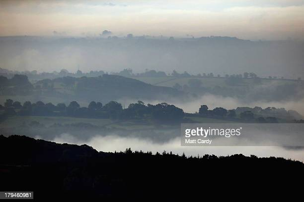 The dawn sun begins to clear the mist and fog lingering in fields close to the city of Wells on September 4 2013 in Somerset England Parts of the UK...