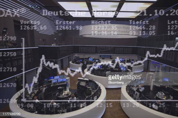 Multiple exposures were combined in camera to produce this image.) The DAX Index curve is displayed over traders working in trading floor pods in a...