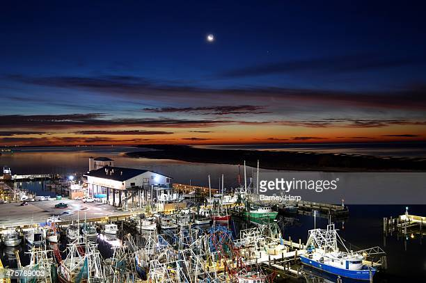 CONTENT] The day breaks over the Gulf ocean water as the moon moves over shrimp boat fleet at dock in Biloxi near the Hard Rock Casino
